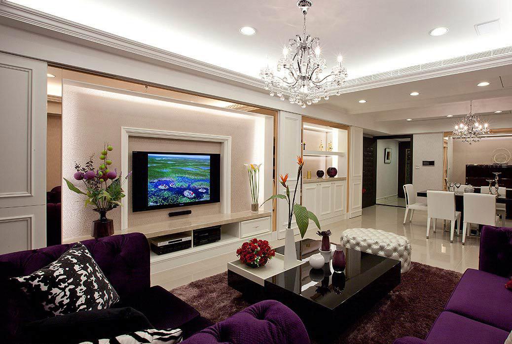影视墙以金色边框进行装饰,紫色的沙发,紫色的窗帘,金色和紫色都是
