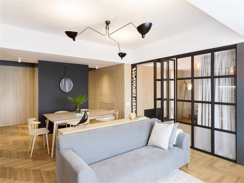冷酷的深灰色金属元素与周围形成强烈对比,成为整个室内的亮点:门廊、厨房、玻璃门一集客厅上方的黑色吊灯一同建立起一道分水岭将不同的区域分隔开来