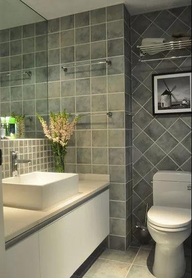 卫生间以蓝灰色的地面+墙面砖,洗手盆前方是镜柜,侧边有2条毛巾挂杆,而马桶后方也是马桶挂杆,整个空间紧凑情调又实用;