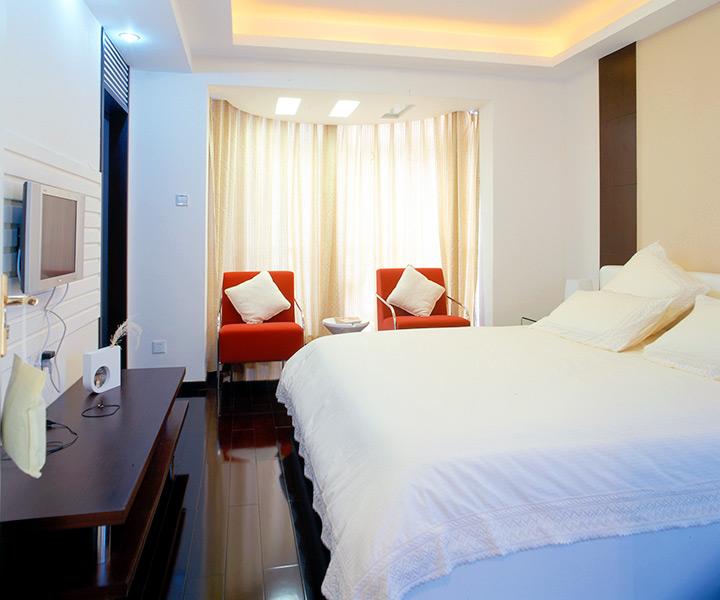 卧室内,装饰元素更加简洁,米白色的床罩让空间显得纯净、柔和,对称分布的深色床背景则增添空间的沉稳和安宁,红色沙发是色彩跳动的音符,纱质落地窗帘形成了色彩、空间上的连接和过度,给人以温馨和浪漫的感觉。
