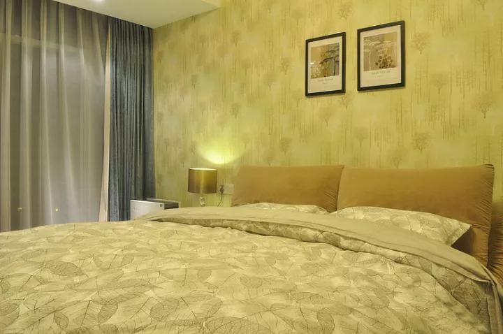 主卧以独特的暖色调壁纸为床头壁纸,树叶图案的床单,整体给人以稳重温馨的感觉;