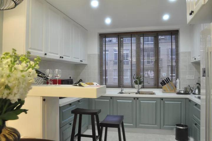 开放式的厨房,与餐厅隔着一个腾空吧台,蓝灰色的橱柜+白色吊柜,宽敞的U型厨房,让做饭的空间舒适又轻松;