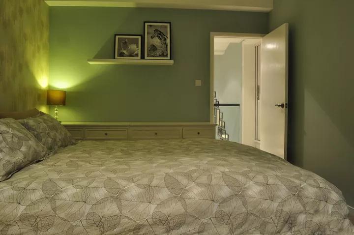 青苹果色的墙面,在靠门的墙面装了一条隔板架,摆上2张照片,美观又情调宽敞;