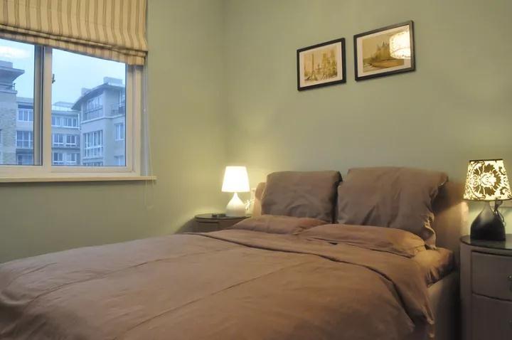 次卧则以蓝灰色的乳胶漆作为签名改,粉褐色的床头与竖纹拉帘的窗帘,搭配出一个轻松舒适的休息空间;