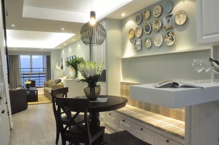 玄关进来的左侧是餐厅、厨房、楼梯区域,以情调温馨的小资调调装修,卡座下方是实用的收纳,而卡座后面的墙面则装上情调优雅的挂盘,搭配一套实木餐桌,圆形铁艺灯罩的吊灯,显得优雅而又精致大方;