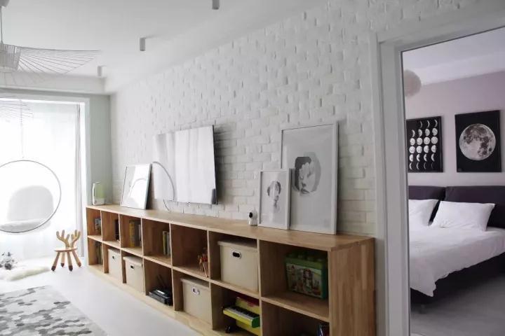 电视墙贴满了白色文化砖,在电视下方则是装了一排开放的原木书架,桌面上摆着几幅极简装饰画,呈现出一个优雅文艺的气息;