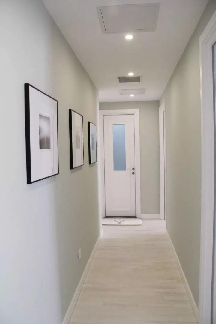 走廊的整体装修简单简洁,天花装了几盏射灯,同时在墙面挂上几幅简约现代的装饰画,整体显得格外的舒适时尚;