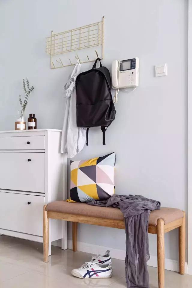 这是入户的玄关,虽说是简简单单的布置,白色的宜家风鞋柜,木质软包换鞋凳,墙壁上金属质感的挂钩置物架,但这样的搭配很清新,重要的是也很实用。