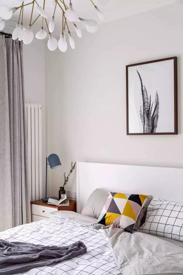 ◆主卧的墙面刷成了淡淡的米色,软装上是白色的木床,再搭配上白色的格子床被,浅色系的卧室空间或许有点单调,不过北欧风的靠枕就能完美解决,留下的就是一个柔软舒适的卧室了。