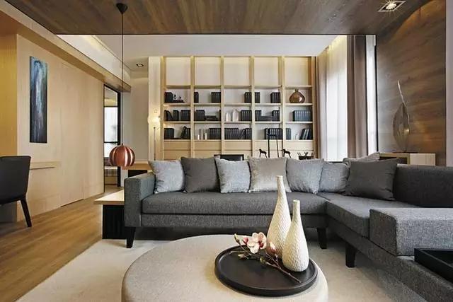 烟灰色的布艺沙发整体给人中规中矩的感觉,圆形的茶几上面三两个装饰品起到恰到好处的装点效果,沙发一侧低垂的吊灯设计别具匠心,十分吸引眼球。