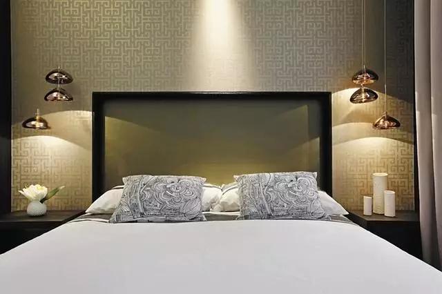 卧室的设计延续了简约的风格,黑白搭配的床品简单、纯粹,透明质感的床头造型实属罕见,床头背景的设计带着些许孤单的气息,床头两侧的低垂吊灯足以满足业主夜读的需要。