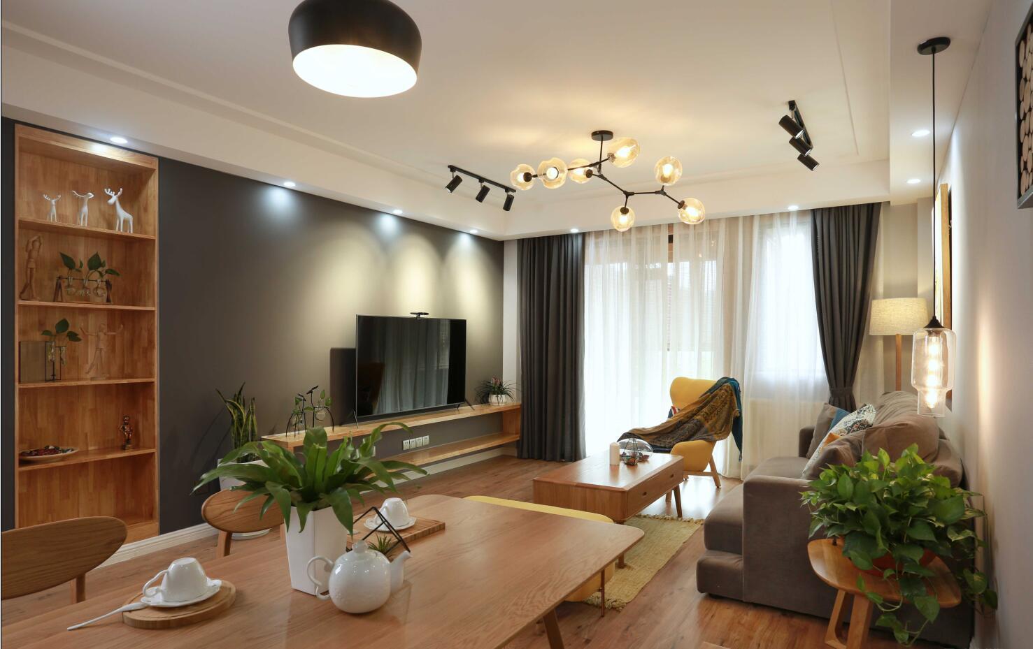 装修设计—(设计预约:182-9186-6197)业主是一对小夫妻,舒适安静的生活是他们所向往的,设计师根据业主的需求,见面沟通后,最终确定为简约、舒适的北欧风格。小夫妻都喜欢北欧风,喜欢回到家那种轻松的感觉、所以委托设计师将整个空间打造的舒适自然。浅咖与原木,浅咖与暖黄,一切都是暖暖的。树枝形玻璃泡泡球客厅灯,搭配两盏吊灯,加上旁边垂下来的圆桶灯,时尚感爆棚。客厅没有太多的繁琐装饰,最终形成了独具特色的北欧风格。它代表了一种回归自然的时尚美。业主不喜欢繁杂的东西,这也体现在电视墙上。把注重舒适度体验感放在首位,灰咖的电视背景墙加上三盏射灯,一场小确型的短剧也能看出文艺大片的感觉。