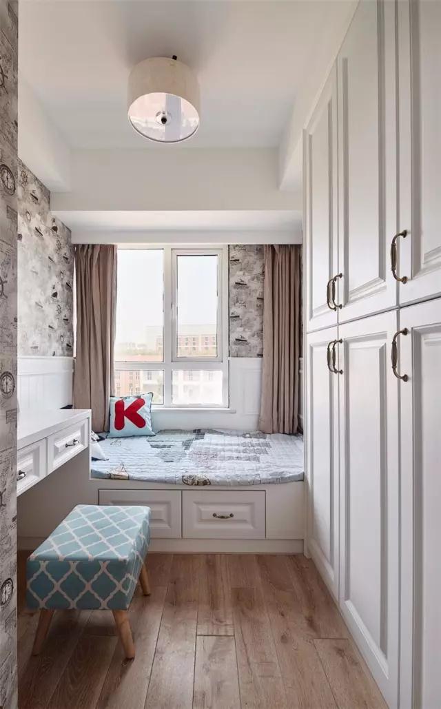 儿童房的墙面贴上黑白灰的复古质感壁纸,靠窗的榻榻米床,在床边的墙面还做了护墙板;在衣柜对面则装了一张书桌,方便孩子在家学习;