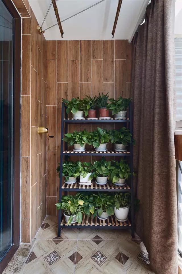阳台的墙面贴着仿木纹的墙砖,而地面则是复古范的地砖,靠墙摆上一个植物架,摆满绿植显得清新自然舒适;