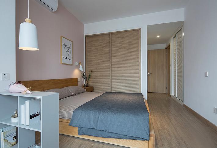 卧室粉色的背景墙可以看出业主粉嫩可爱的内心,木地板与门的花纹相似,衣柜的推拉门和床也都是原木色,日式自然随意的味道蔓延在整个卧室里。