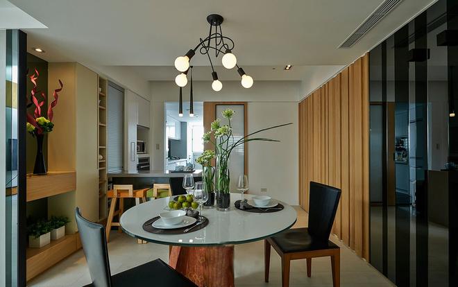 圆桌餐桌能容纳多人一起进餐,黑色镜面的墙面折射空间之中的灯光,厨房与餐厅之间用吧台隔断,厨房的阳光打在吧台上,阳光既不会太刺眼,空间也不会过于昏暗。吧台同样适合小夫妻两人的额正常使用。