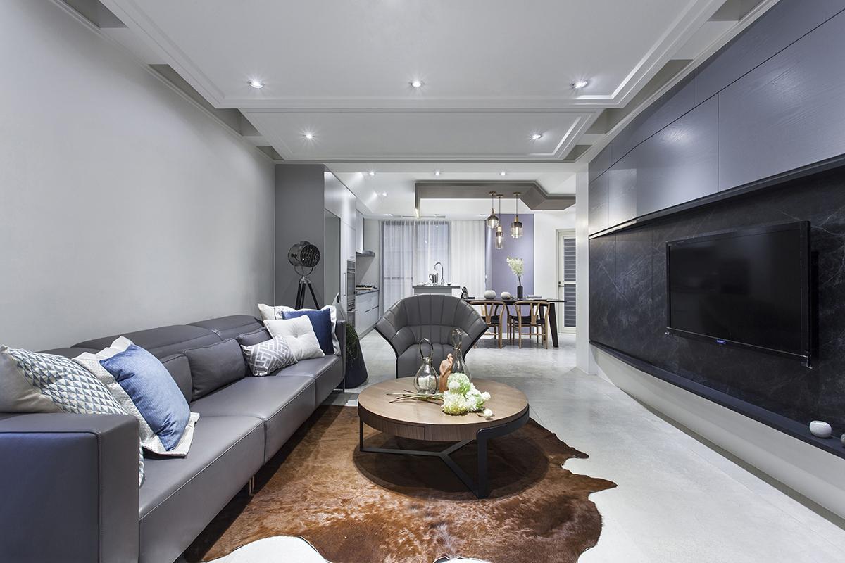 客厅面积不大,适合小众聚会,吊顶造型独特,灰白色的空间在视觉上更具层次感,灰紫色的皮质沙发与背景墙相呼应,在风格上更为一致,特点鲜明不简单,茶几底部貂皮材质的不规则地毯是整个屋子亮点的地方,配色上与整体相冲,但材质却显得客厅优雅高级,并不鹤立独行,而是从其他方面衬托这个屋子独特的风格。